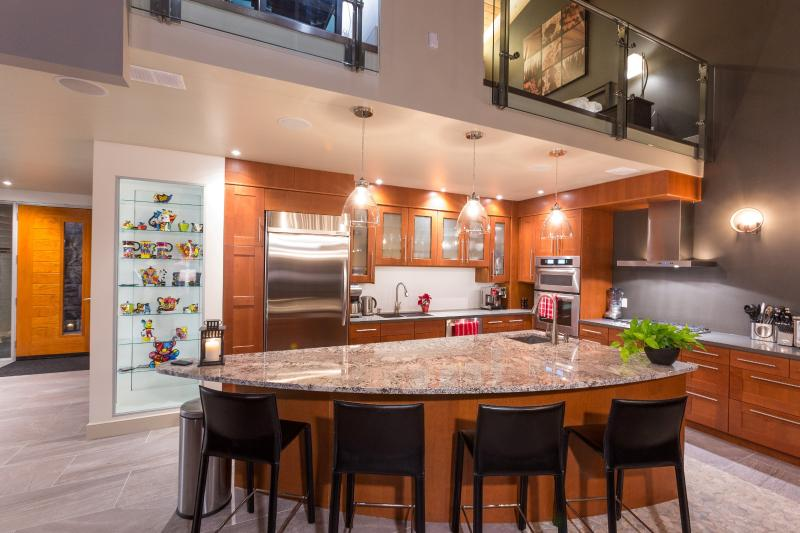 Chef's kitchen completely outfitted with large and small appliances including beverage fridge.