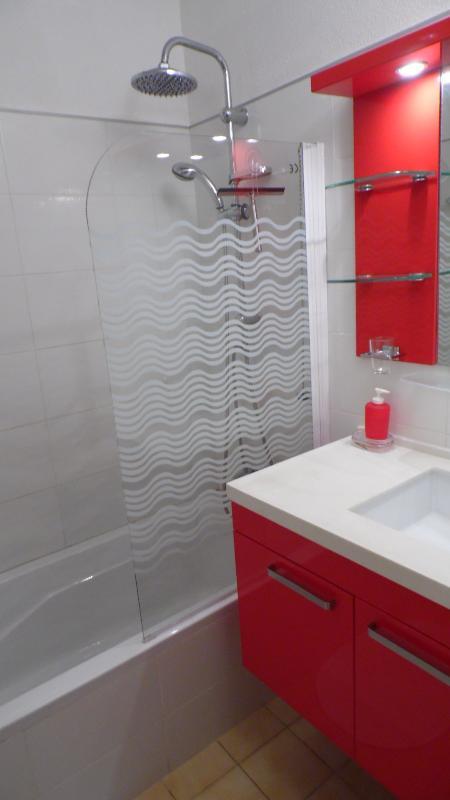 salle de bains installée avec baignoire/douche et meuble vasque.