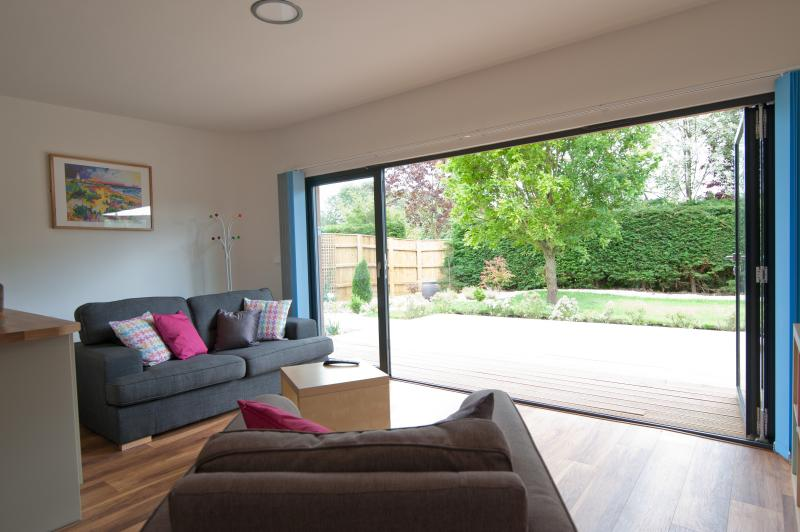 Bi-fold doors open onto the wide sun-deck and private garden
