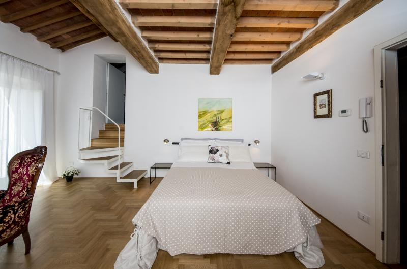 Un lit double dans une chambre à coucher FLOU par le style toscan, avec toutes les commodités