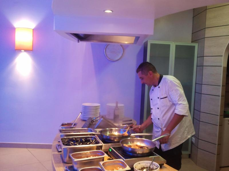 Chef preparing mouth watering fish, pasta, meat and pizza dishes
