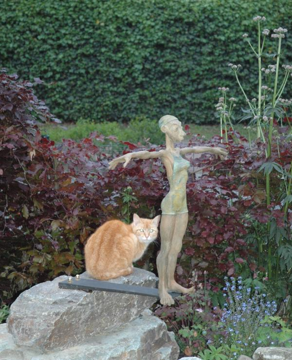bronze statuette in front garden , wooden furniture there to sit and relax