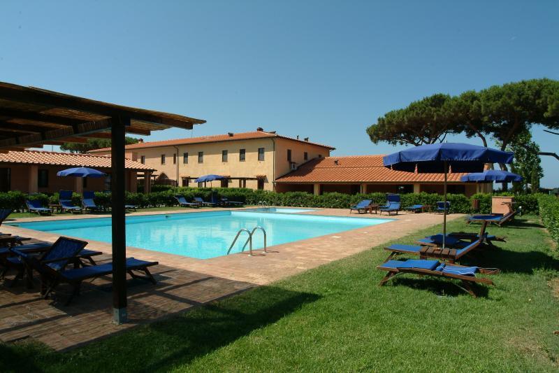 Area solarium e piscina attrezzata con lettini e ombrelloni