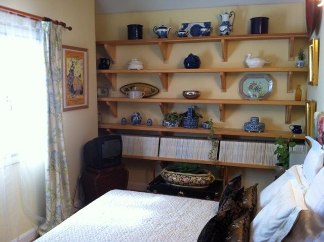 Double bed with wall wood shelves with our favorite ceramics and Architectural Digest collection