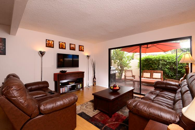Living room with 47' smart LG TV, video player, cable service and patio beyond