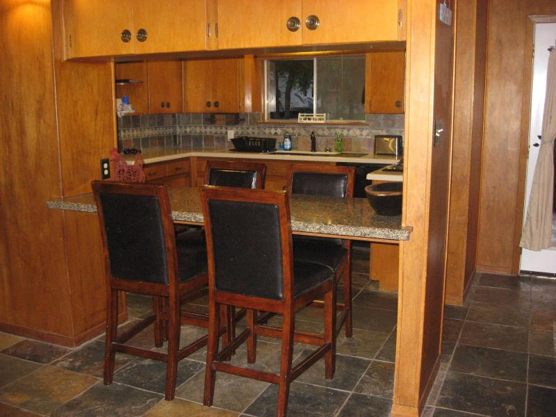 Additional dining area for 4 adjacent to the other table and the kitchen.