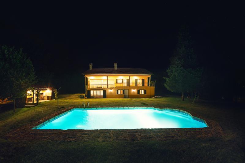 Casa a noite com piscina iluminada
