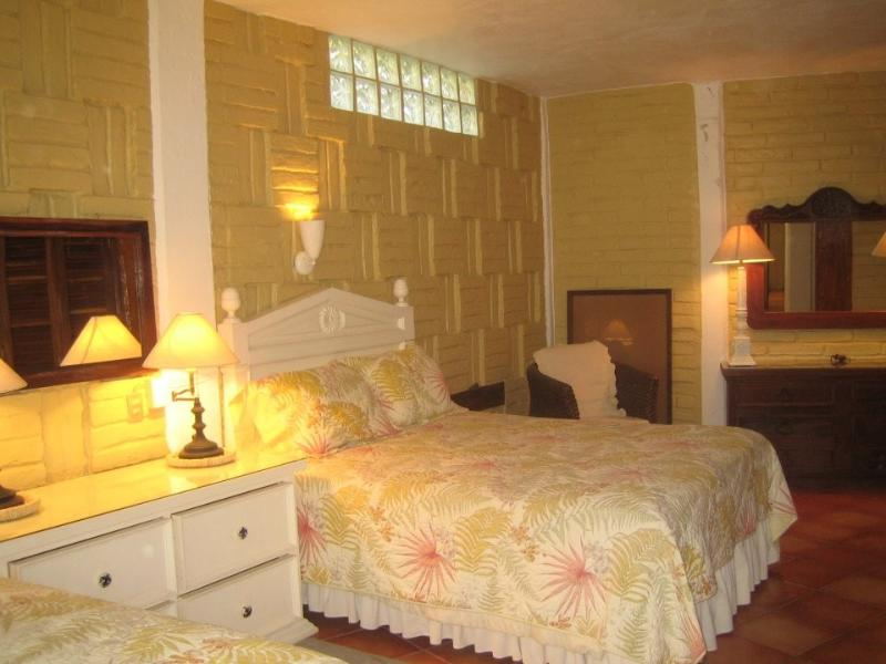 The yellow bedroom has two queen-sized beds.