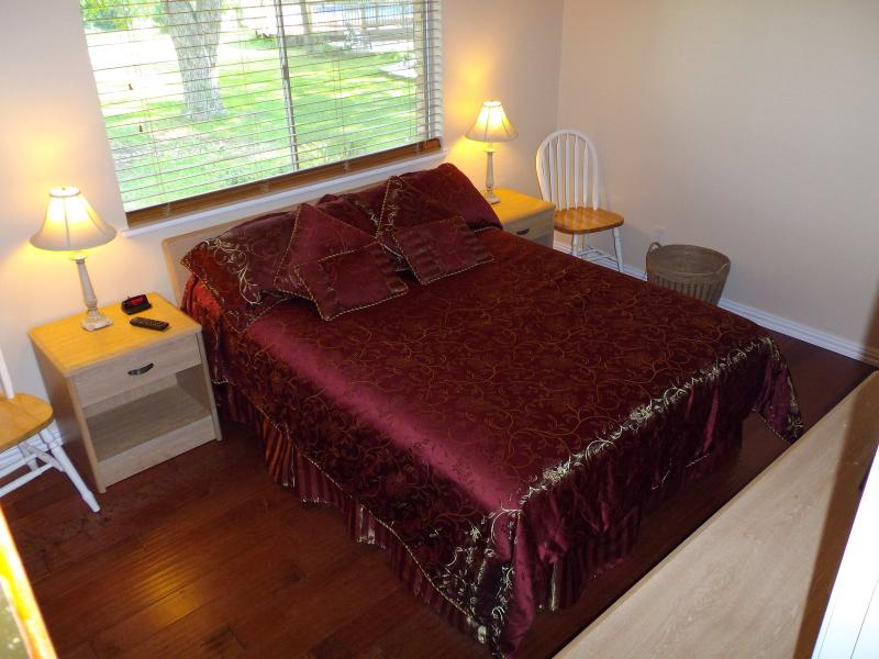 Third bedroom queen bed with view of backyard.