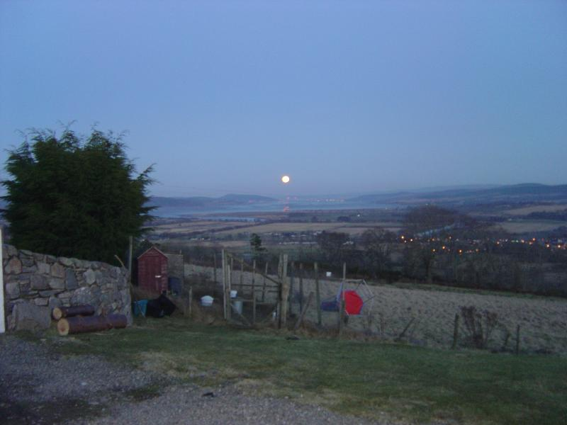 Early evening in Spring with a full moon just rising over Inverness 12 miles away
