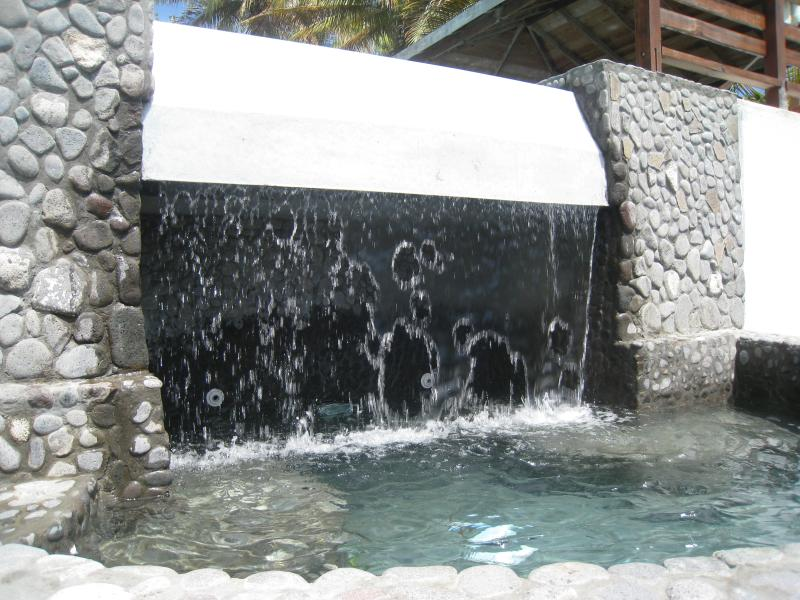The waterfall from the main pool dropping into the beautiful pebbled kids pool