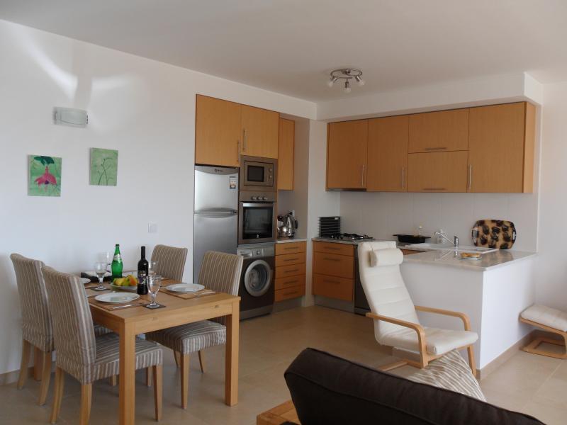 Mesa de comedor y zona de cocina en la sala de estar