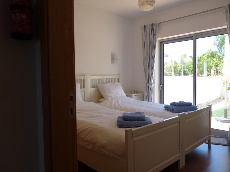 2 dormitorios con camas y puerta del patio jardín