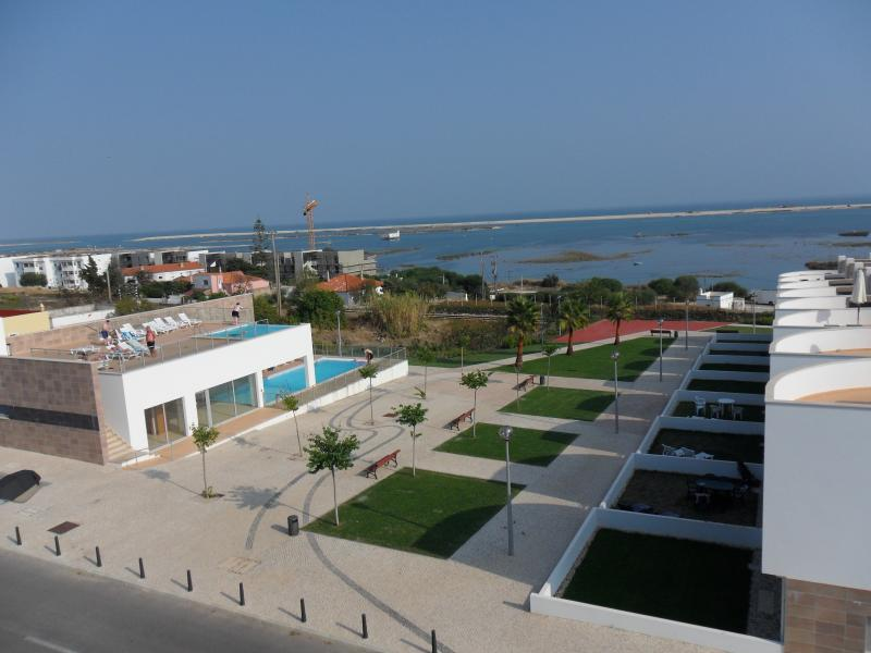 Vista desde el bloque de apartamentos de la zona de piscina, jardines y Ria Formosa con la marea alta