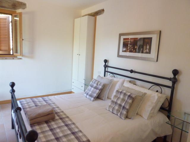 The master bedroom with large double bed, ample fitted storage and glazed doors onto the garden