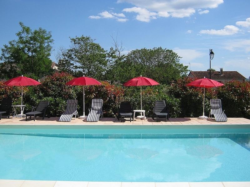Swimming-Pool mit Liegestühlen und Sonnenschirmen