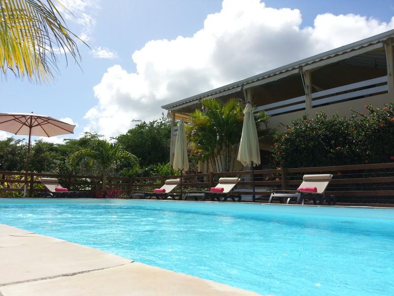 Vue extérieure de la Villa Malaka, piscine et solarium équipée de transats et parasols