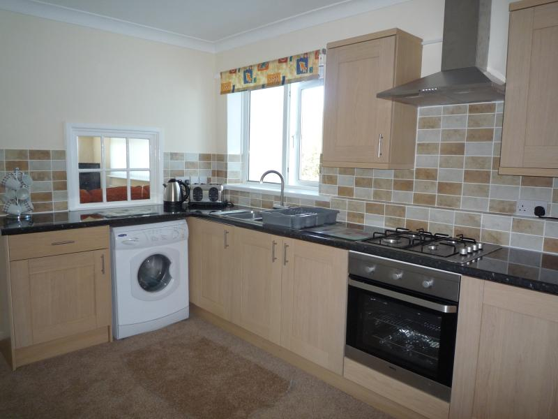 Kitchen with built in oven and hob, fridge freezer, and washing machine