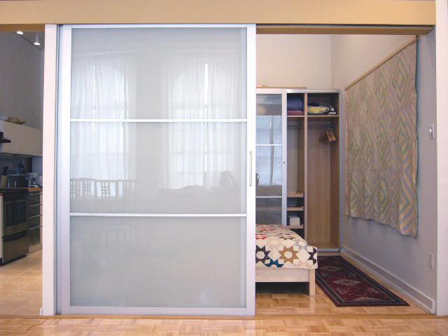 bedroom with queen bed with opaque sliding glass door open