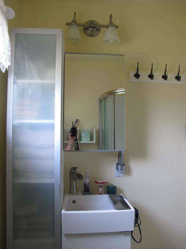 Brand new bathroom vanity, and high cabinet stocked with bathroom essentials.
