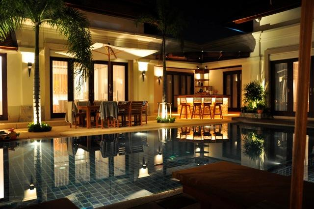 Across the pool at night with outside Bar