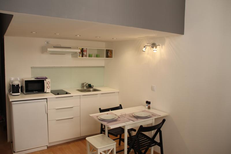 Kitchen with microwave, fridge, coffee machine and dishes