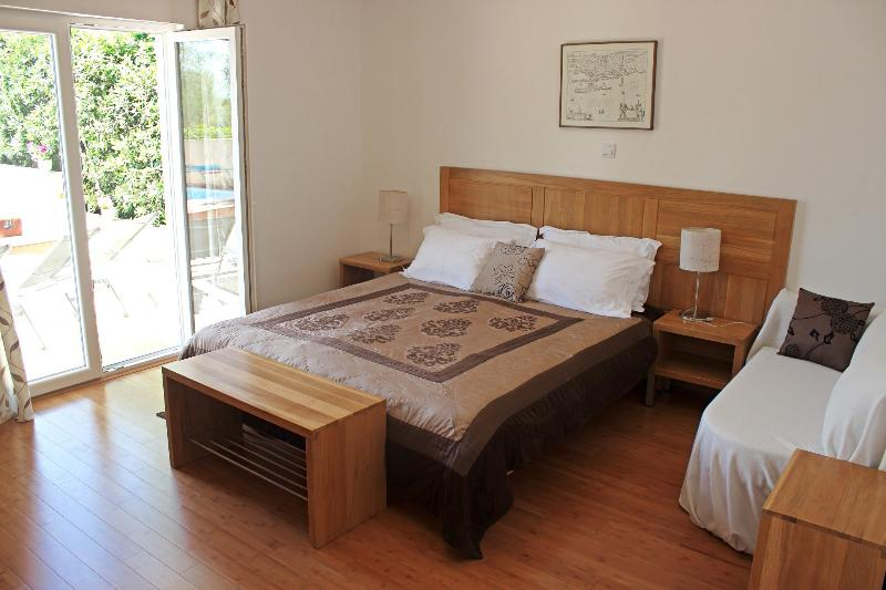 Ground floor double bedroom with extra single sofa bed has direct access to the swimming pool area