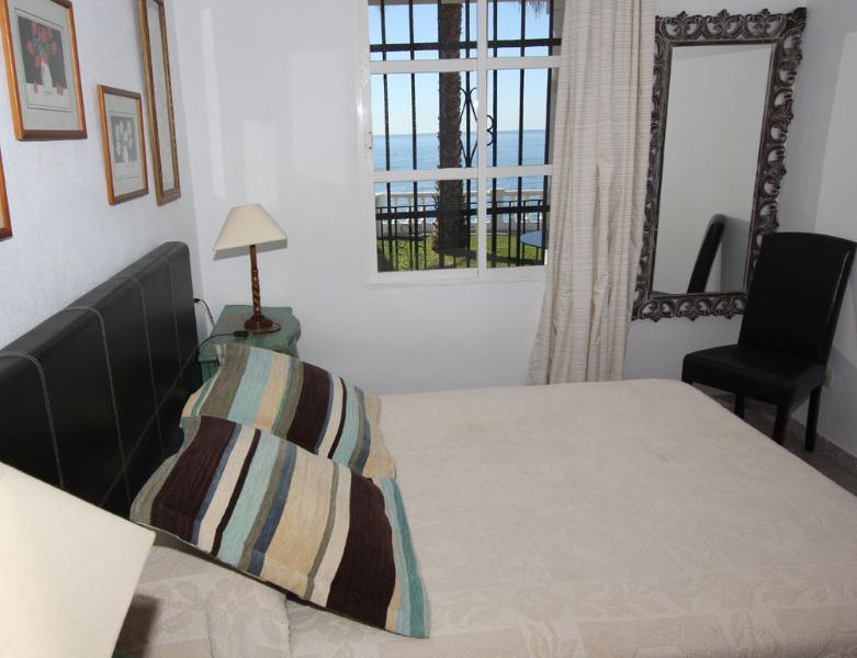 Dormitorio con cama de matrimonio y vistas al mar