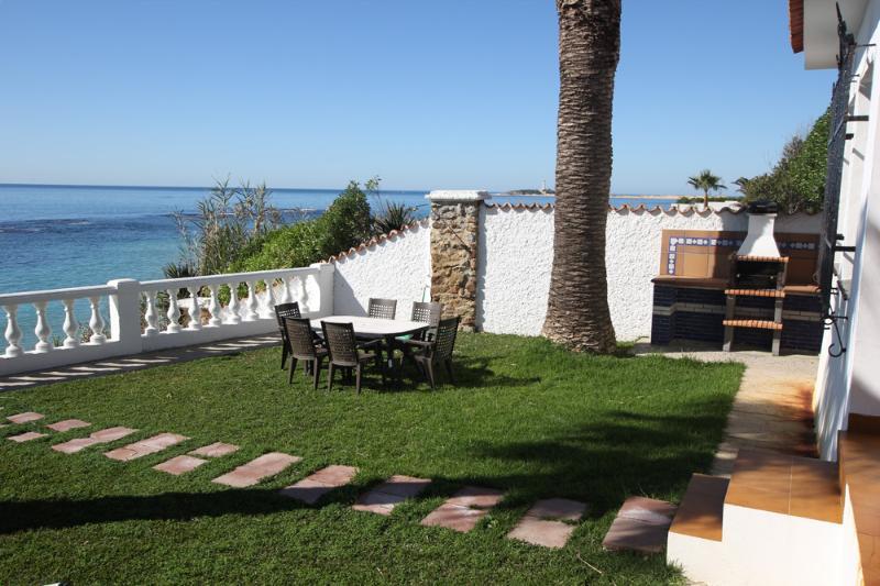 Jardín privado totalmente independiente con gran barbacoa de obra y mobiliario de jardín.
