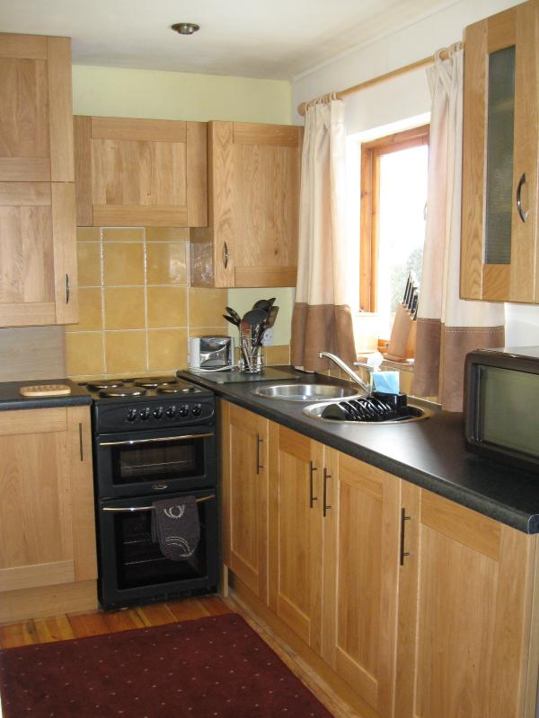 Kitchen with units, cooker, microwave, and fridge freezer.