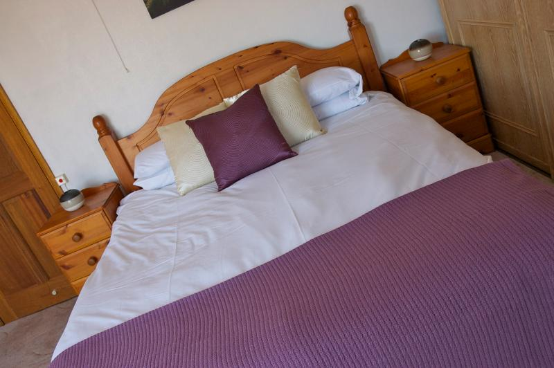 bedroom sleeping four comprising of one large double and two single beds.