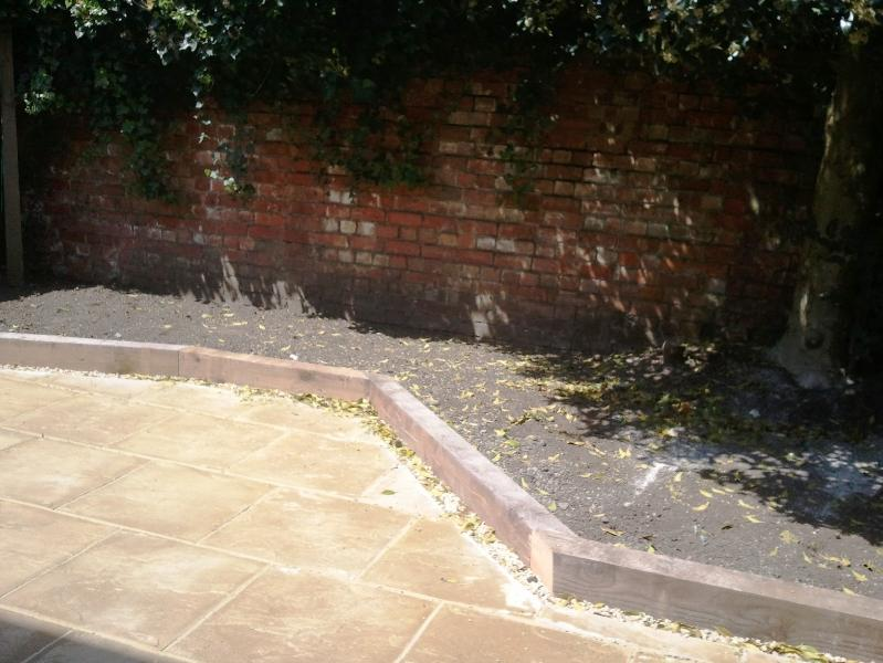 Paved sunny rear garden with table and chairs in the Spring/Summer