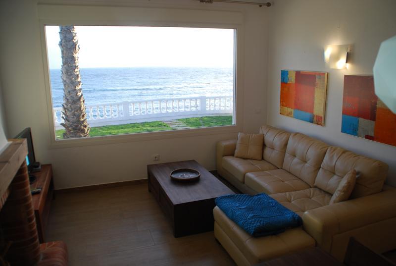 Amplio salon con sofá cheslong, chimenea, TV satélite, wifi y vistas al mar.