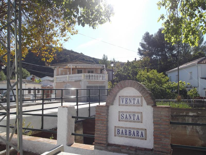 The towns bridge and name plate with Casa Cinco in the background