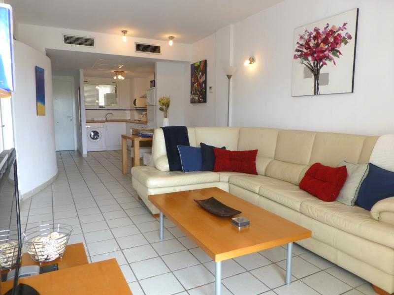 Lounge with corner suite, flat screen TV. Bright and airy with patio doors leading to balcony