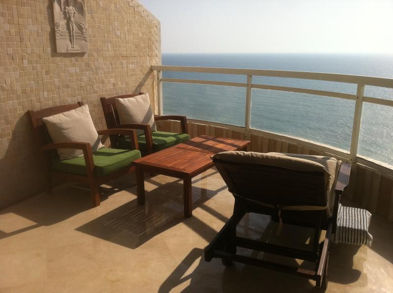 large balcony, coffee table and sunbed, sunset time