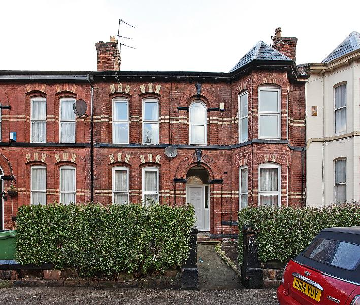 The property is the top flat of a terraced house on a residential street with free on-street parking