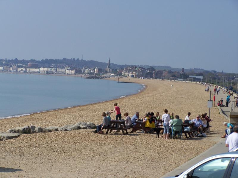 Overcombe beach. Oasis Cafe tables and promenade (next to Paradise Villa).