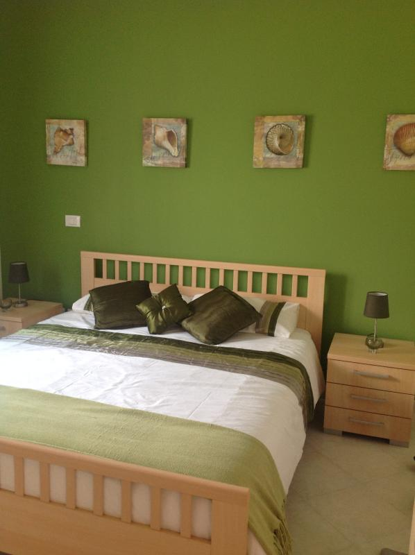 Master en suite bedroom with king-size bed, wardrobes and chest of drawers