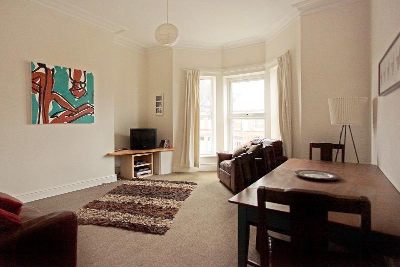 Grande, luminoso e arioso soggiorno con grande tavolo da pranzo, divano in pelle e poltrona