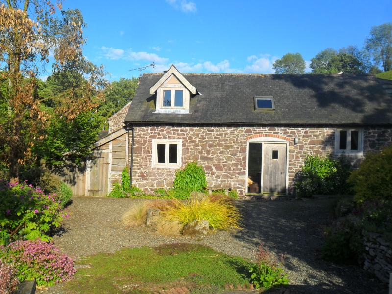 Stone built byre with private paved and gravel garden, surrounded by shrubs and flowers.