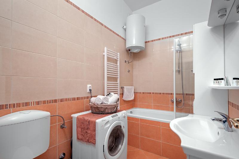 Bathroom with bath/shower, vanity and washing machine