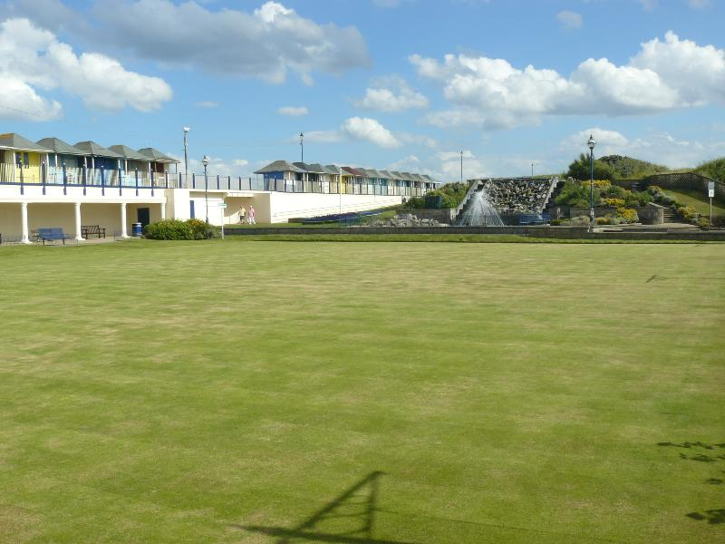 Sutton-on-Sea bowling green, gardens and beach huts on the promenade.