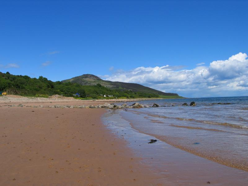 Praia da Baía de badejo com ilha sagrada da distância