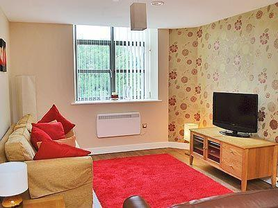 Spacious lounge with TV, comfy sofas and snuggly cushions