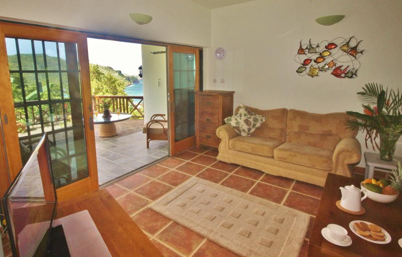 The living area has patio doors leading onto a covered patio with beautiful views of the sea