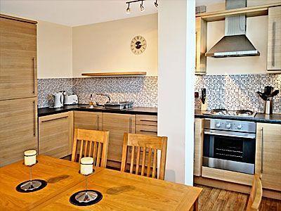 Sala de jantar com furnture Carvalho fornecendo assentos para seis comentários e totalmente equipada cozinha