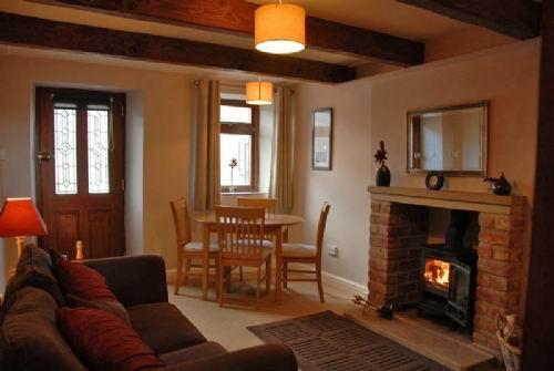 Feature-Lounge / Diner mit Eichenbalken und bequemen Sofa, zusammen mit einem holzbeheizten Ofen.
