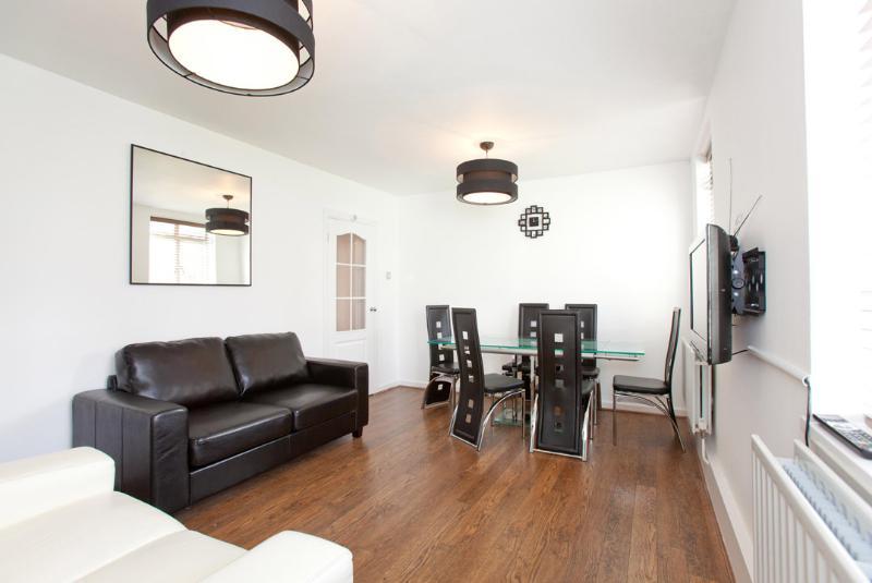 Rm di ampia reception con parete montato al plasma tv, tavolo da pranzo in vetro, divano 3 posti letto e 2 posti