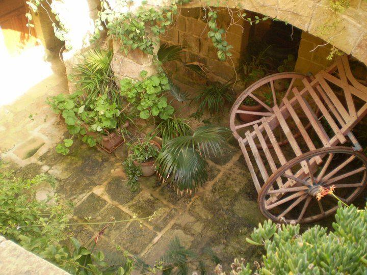 An internal yard with a traditional Maltese cart and colourful 'Sardinell' flowers.